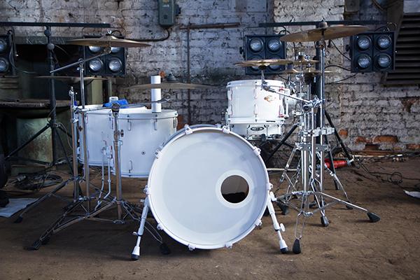 white drum set in industrial room on white brick background grunge